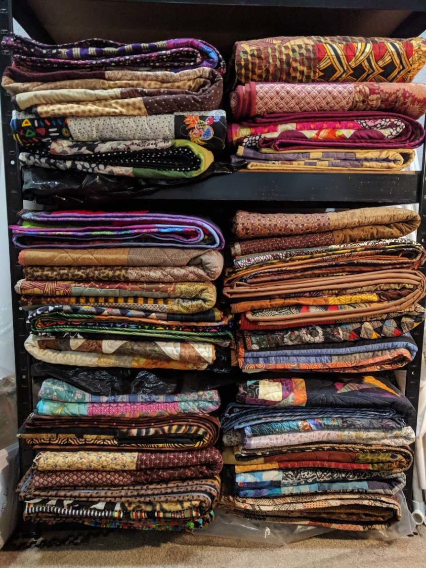 Two stacks of colorful, folded quilts
