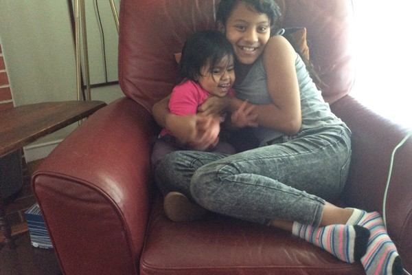 photo of two young girls cuddling on a chair