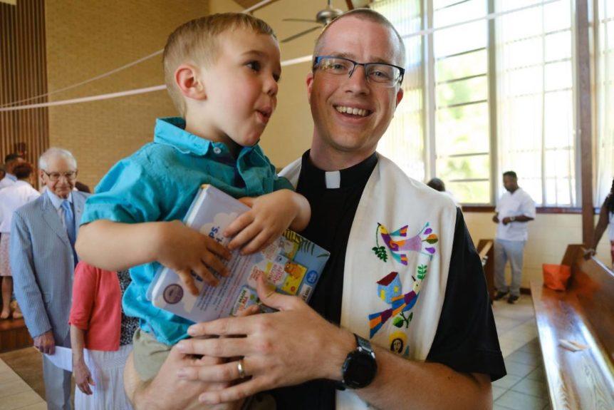 pastor ben groth holding child