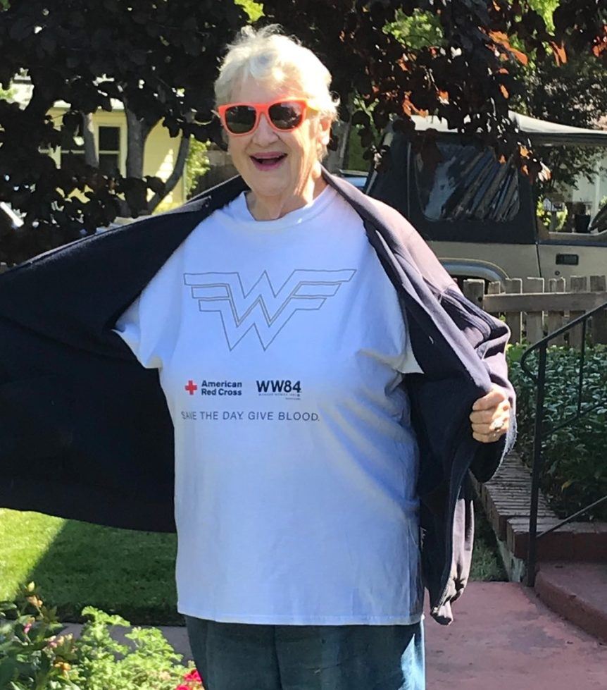 """smiling elderly woman wearing sunglasses opening her coat to reveal t-shirt with a wonder woman logo and text that says """"save the day, give blood"""""""